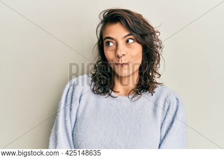 Young hispanic woman wearing casual winter sweater smiling looking to the side and staring away thinking.