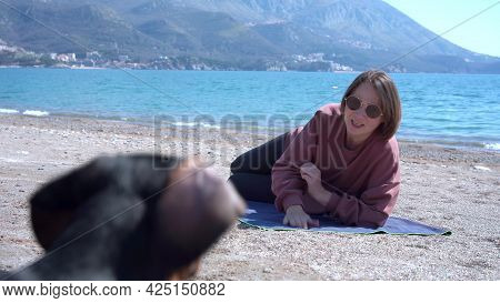 Smiling Woman With Sunglasses Calls Dachshund Puppy To Sit On Mat On Sand Beach Against Azure Sea An