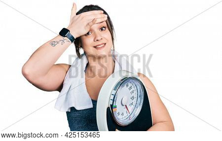 Young hispanic girl wearing sportswear holding weighing machine stressed and frustrated with hand on head, surprised and angry face