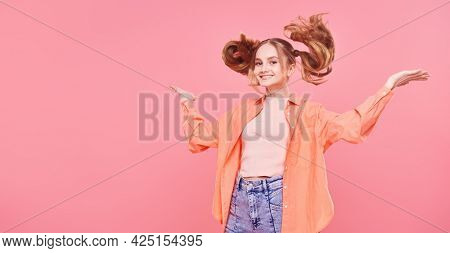 Portrait of a carefree girl teenager with funny ponytails jumping on a pink background. Youth style. Fashion. Copy pace.