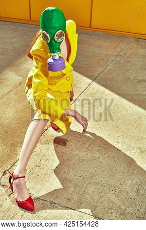 Full length portrait of a woman in elegant yellow suit and green gas mask posing by a yellow industrial wall. Fashion of the future. Environmental disaster, apocalypse.