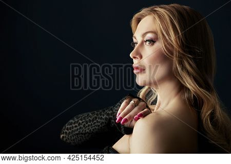 Portrait of a wealthy middle-aged woman with evening makeup and hairstyle posing in black dress on a black background. Copy space. Luxury lifestyle. Cosmetology, plastic surgery, rejuvenation.