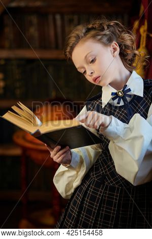 Kid's school fashion. Cute eight year old girl in elegant classic school uniform reads a book in a luxurious vintage room.