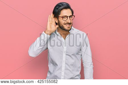 Young hispanic man wearing business shirt and glasses smiling with hand over ear listening an hearing to rumor or gossip. deafness concept.