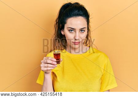 Young hispanic woman drinking whiskey shot thinking attitude and sober expression looking self confident