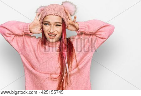 Young caucasian woman wearing casual clothes and wool cap trying to hear both hands on ear gesture, curious for gossip. hearing problem, deaf