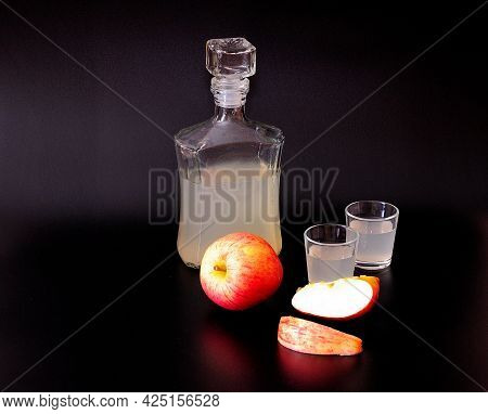 Two Glasses And A Bottle Of Calvados, With Pieces Of Fruit On A Black Background, Strong Alcohol Bas