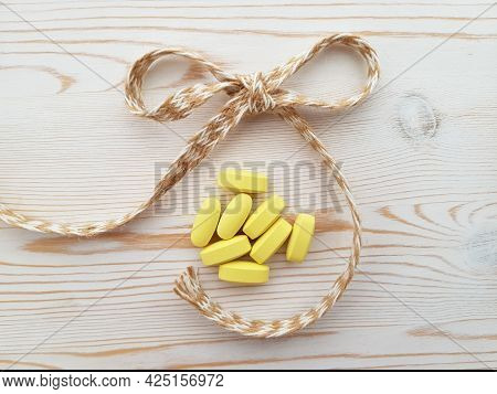 A Handful Of Vitamins, Tablets And A Jute Linen Bow On A Light Background With A Wooden Texture.