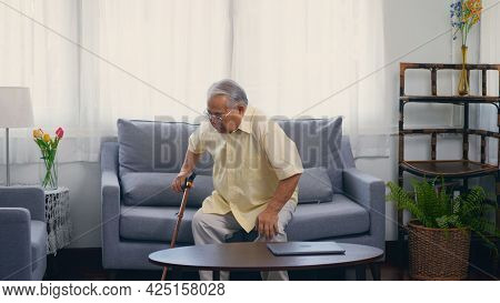 Old Man Grandfather With Eyeglasses Used A Walking Stick To Lean The Ground Slowly Stand Up From The