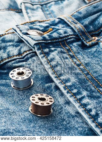 Blue Jeans, Metal Spools Of Thread, Close-up. Tailoring Of Casual Denim Clothing Concept. Cutting An