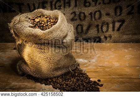 Fresh Roasted Coffee Beans In A Hessian Sack On A Rustic Wood Floor With Hessian Background With Ste