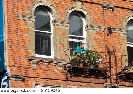 Auckland New Zealand - June 19 2021; Woman In Blue Tends Flower Through Window In Traditional Red Br