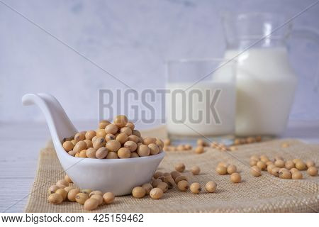 Close Up Tasty Organic Homemade Soy Milk In Glass And Soybean Or Soya Beans In Glass Bowl On A Woode