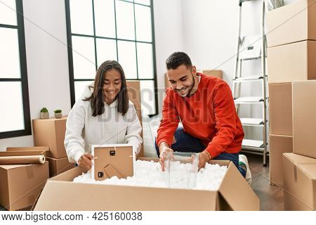 Young latin couple smiling happy unboxing cardboard box at new home.