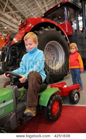 Boy Astride A Small Tractor The Girl Standing Behind