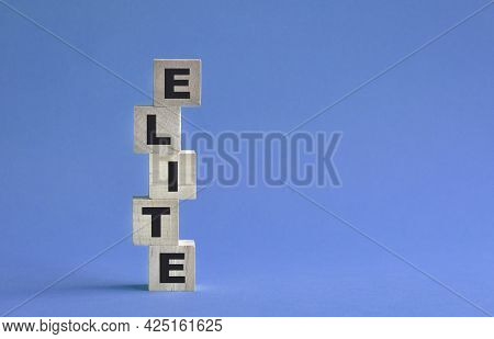 Elite Word Written On Stacked Up Wooden Cubes. On Blue Background.