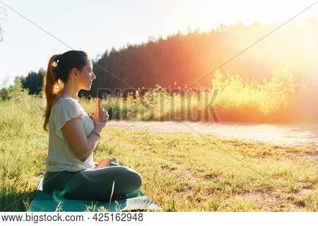 Yoga In Nature. Beautiful Young Woman Practicing Yoga Asana Meditating In Lotus Position, Amazing Su