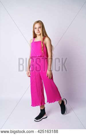 Beautiful Girl Teenager Posing In A Pink Jumpsuit On A White Background. Stylish And Youthful Bright