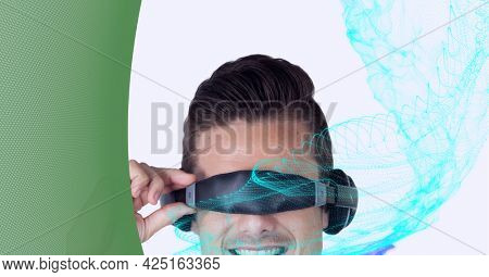 Composition of digital light trails with man wearing vr headset. global digital interface, technology and networking concept digitally generated image.