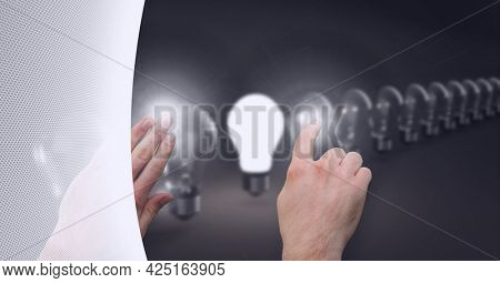 Composition of person touching lit light bulb with row of light bulbs on grey background. global digital interface, technology and networking concept digitally generated image.