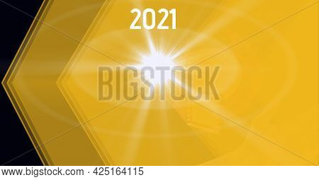 Composition of year 2021 and light flare over translucent layered yellow shapes, on black. business, energy, ideas and eco concept, digitally generated image.