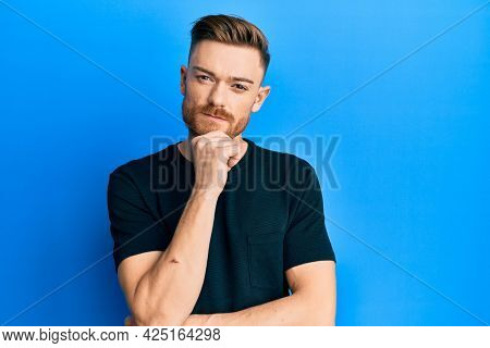 Young redhead man wearing casual black t shirt thinking concentrated about doubt with finger on chin and looking up wondering