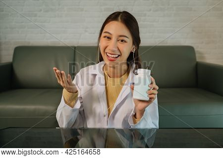 Young Female Doctor With Earphones Inn A Labcoat Sitting In Front Of Laptop Showing Bottle Of Prescr