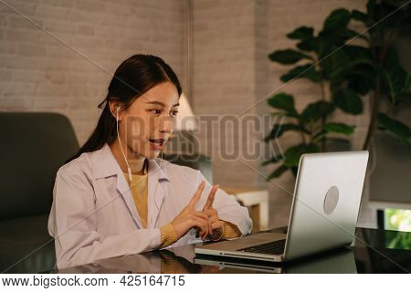 Successful Young Asian Female Doctor With Labcoat And Earphones Doing Video Conference Call For Cons