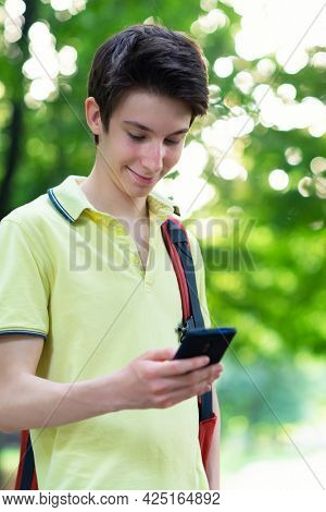 Young handsome boy with headphones using smartphone, summer park outdoor. 15 years old teenager talking and sends messages by mobile phone, youth lifestyle