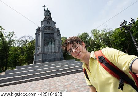 Young handsome 15 years old teen boy looking at camera and happy smiling takes a selfie with smartphone over monument to Vladimir, summer city centr of Kyiv, Europe