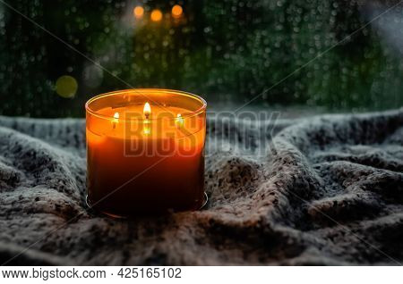 Burning Aroma Candle Puts On Table With Cloth Near By Window That Have Rain Drop In Monsoon Season.