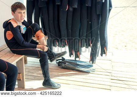 Child Boy Puts On A Wetsuit And Prepares To Dive. Boy Scuba Diver.the Boy Puts On Diving Equipment.