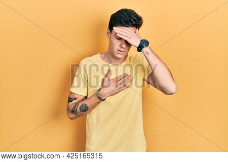 Young hispanic man wearing casual yellow t shirt touching forehead for illness and fever, flu and cold, virus sick