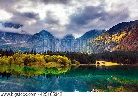 Lake Fuzine in Northern Italy. The Dolomites are covered with clouds. Orange and yellow trees are reflected in the green smooth water. Magnificent colors of autumn.