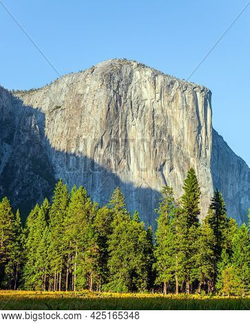 Rock Monolith El Capitan. Majestic cliffs and grassy meadows. Yellow autumn grass in the Yosemite Valley. California, USA. The park is located on the slopes of the Sierra Nevada.