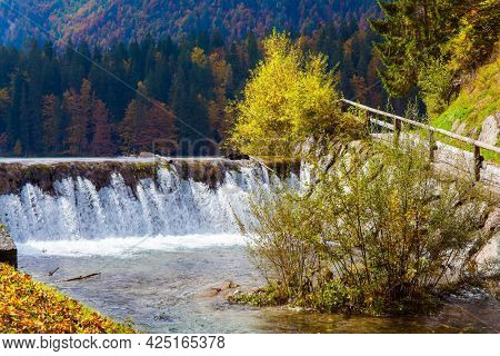 Lake Fuzine waterfall. Yellow and orange trees are reflected in the green smooth water of the lake. Alps. Border between Northern Italy and Slovenia.