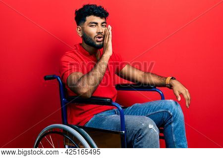 Arab man with beard sitting on wheelchair hand on mouth telling secret rumor, whispering malicious talk conversation