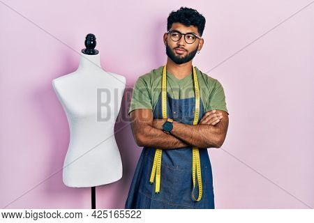 Arab man with beard dressmaker designer wearing atelier apron smiling looking to the side and staring away thinking.