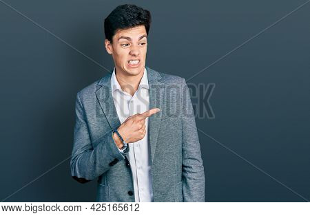 Young hispanic man wearing business clothes pointing aside worried and nervous with forefinger, concerned and surprised expression