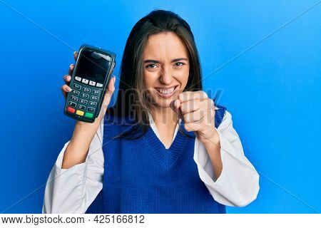 Young hispanic girl holding dataphone annoyed and frustrated shouting with anger, yelling crazy with anger and hand raised