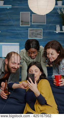 Multiracial Friends Hanging Out Together Socializing While Looking At Funny Video On Smartphone. Gro