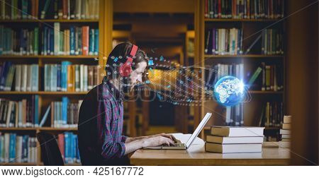 Composition of digital globe over male student using laptop in library. global education, digital interface, technology and networking concept digitally generated image.