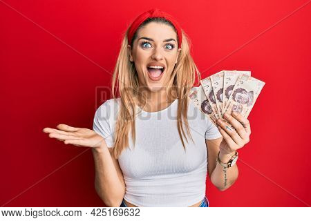 Young caucasian woman holding 500 mexican pesos banknotes celebrating achievement with happy smile and winner expression with raised hand