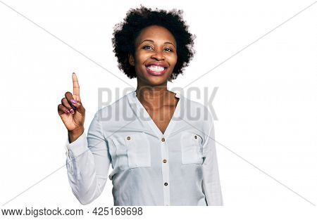 African american woman with afro hair wearing casual white t shirt showing and pointing up with finger number one while smiling confident and happy.