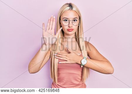 Young blonde girl wearing casual clothes swearing with hand on chest and open palm, making a loyalty promise oath