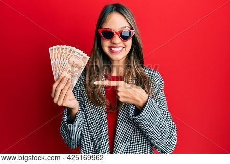 Young brunette woman holding 50 turkish lira banknotes smiling happy pointing with hand and finger