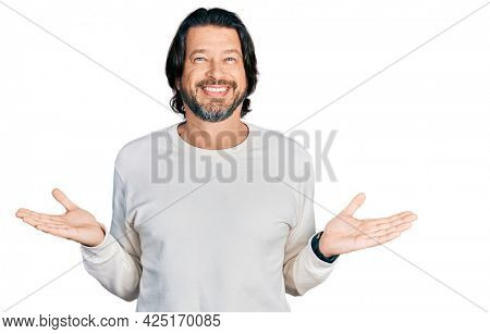 Middle age caucasian man wearing casual clothes smiling showing both hands open palms, presenting and advertising comparison and balance