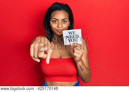 Young african american girl holding we need you paper pointing with finger to the camera and to you, confident gesture looking serious