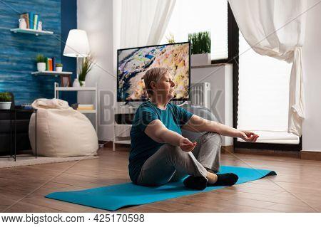 Peaceful Retired Senior Woman Meditate During Meditation Retreat Workout Sitting Comfortable In Lotu
