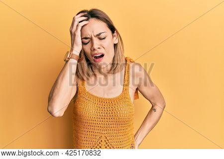 Young caucasian blonde woman wearing casual yellow t shirt yawning tired covering half face, eye and mouth with hand. face hurts in pain.